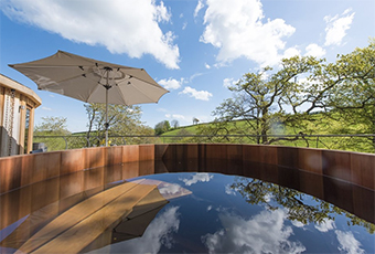 the sky reflected in a hot tub by a rural cottage - Holiday Cottages with a Hot Tub