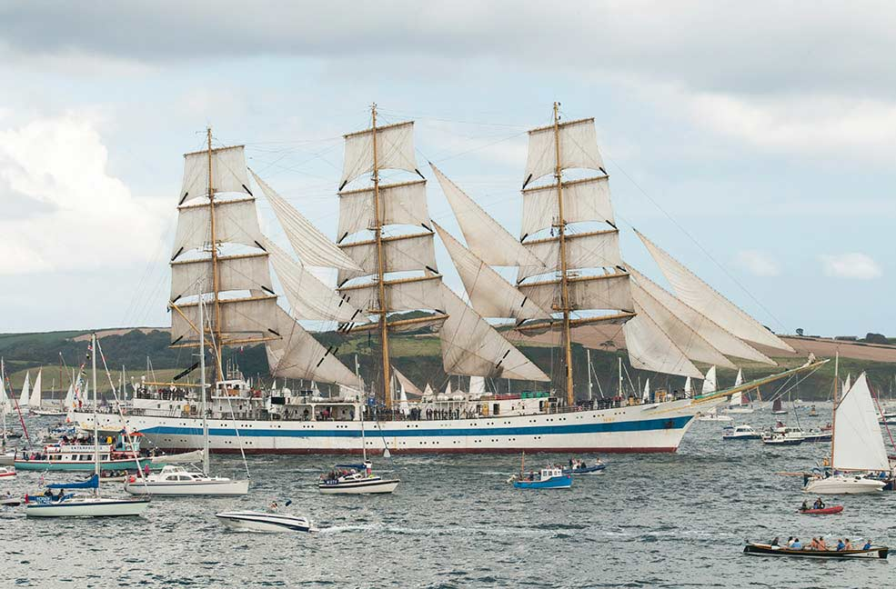 The tall ship dwarfs other water craft