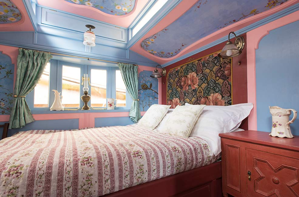 The bedroom is filled with beautiful details including the hand-painted wood panels that brighten up this space with pastel colours and floral patterns.