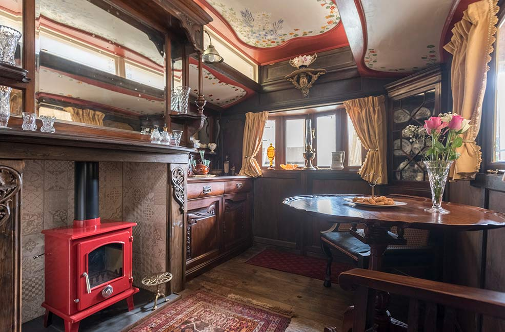 The living area in Sanger's Showman's Wagon in Cornwall has been hand decorated and wood panelled by the owners.