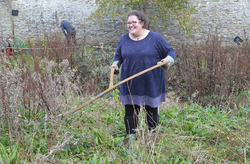 Volunteer with scythe at Penrose in Cornwall