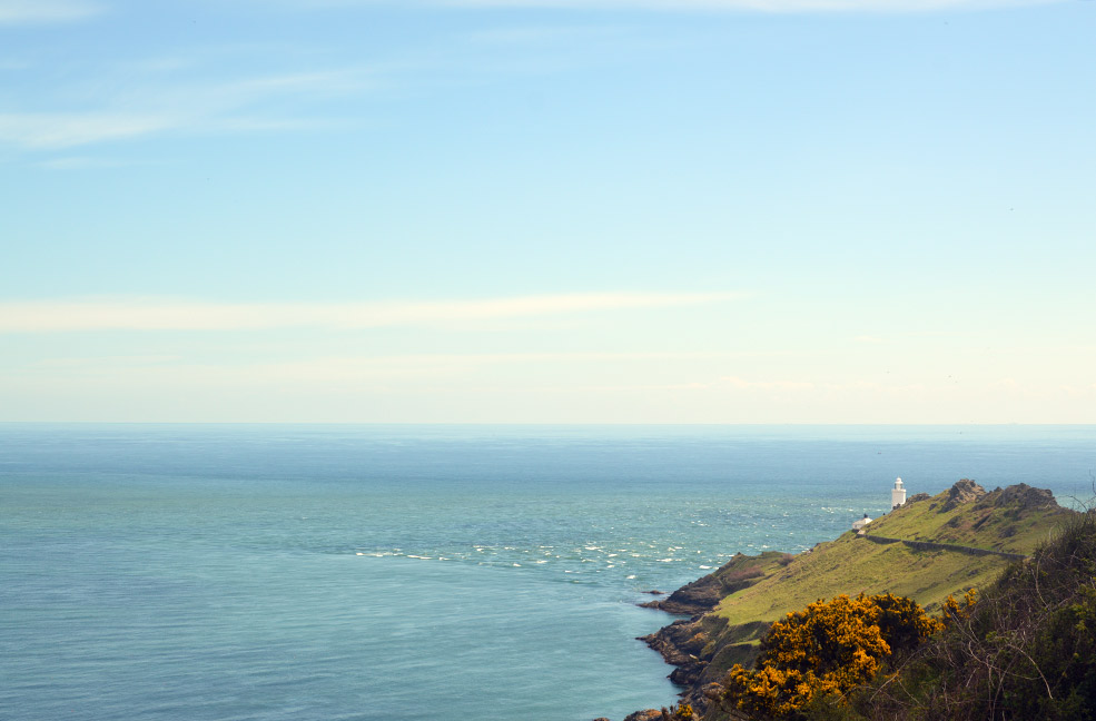 A far away view of Start Point Lighthouse overlooking the beautiful blue sea of Start Bay in South Devon.