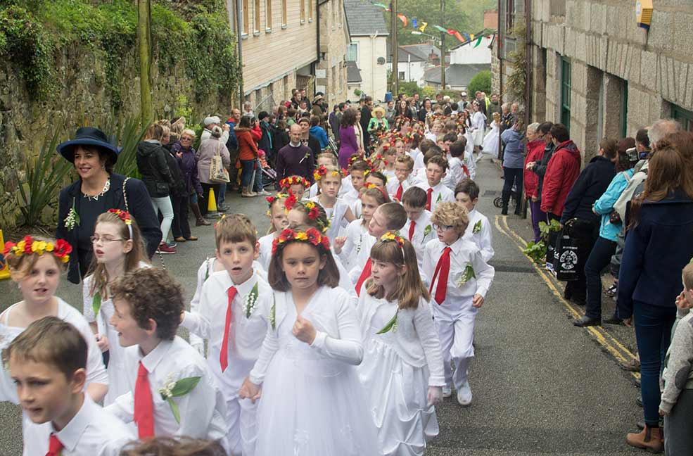 Children dancing in the streets of Helston, Cornwall as part of the Flora Day celebrations.