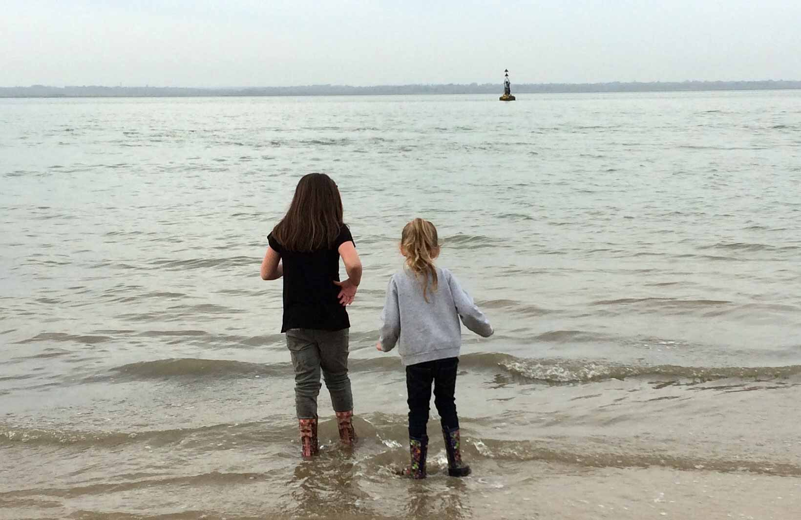 Two little girls wash their muddy wellies while looking out to sea next to Fort Victoria on the Isle of Wight.